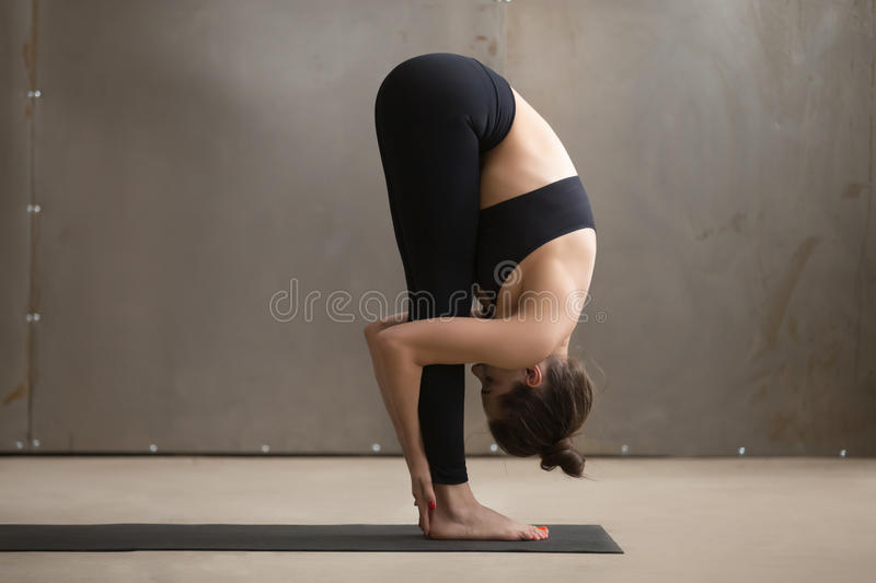 Young attractive woman standing in uttanasana pose, grey studio. Young attractive woman practicing yoga, standing in head to knees, uttanasana exercise, Standing stock images