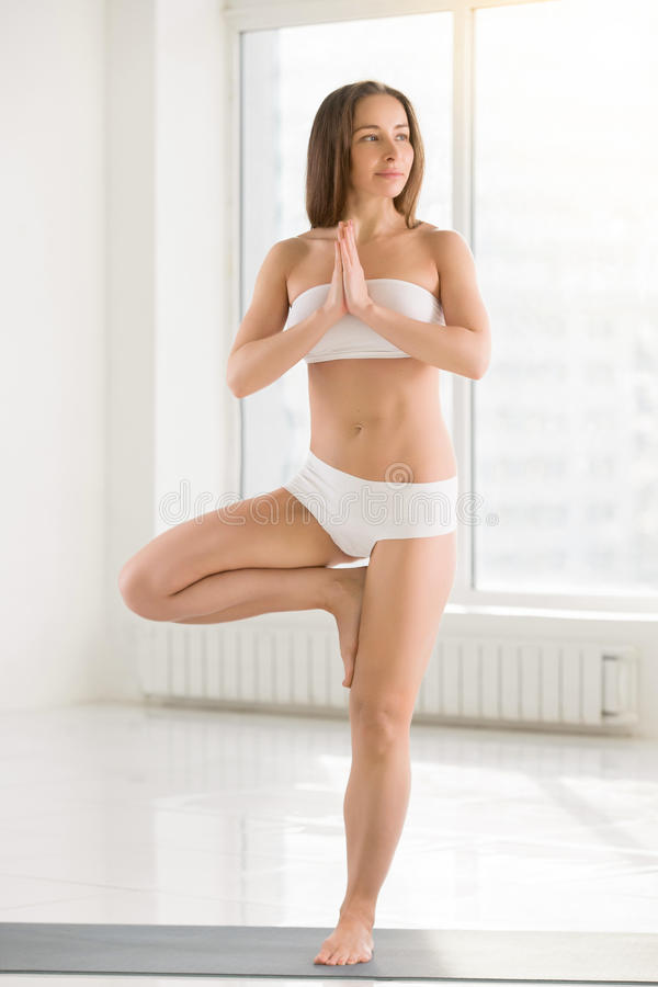 Young attractive woman standing in Vrksasana pose, white color b stock photography