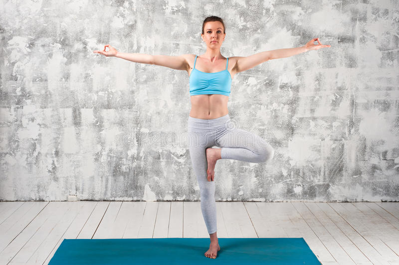 Young attractive woman staying in Yoga Tree Pose royalty free stock photo