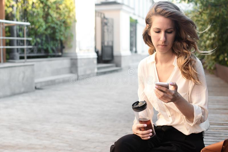 Young attractive woman at park, working with phone, drinking coffee, having lunch in a hurry. Business concept photo stock photos