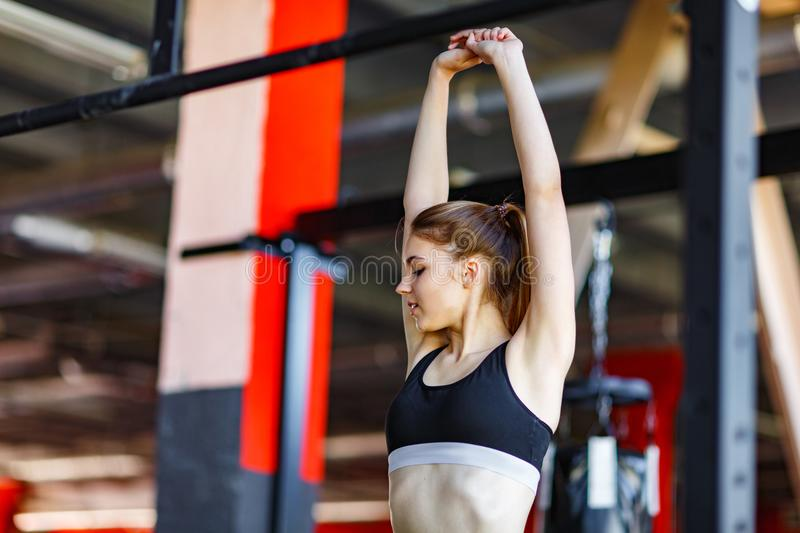 A young attractive woman stretches out her arms, lifting them over her head. royalty free stock photo