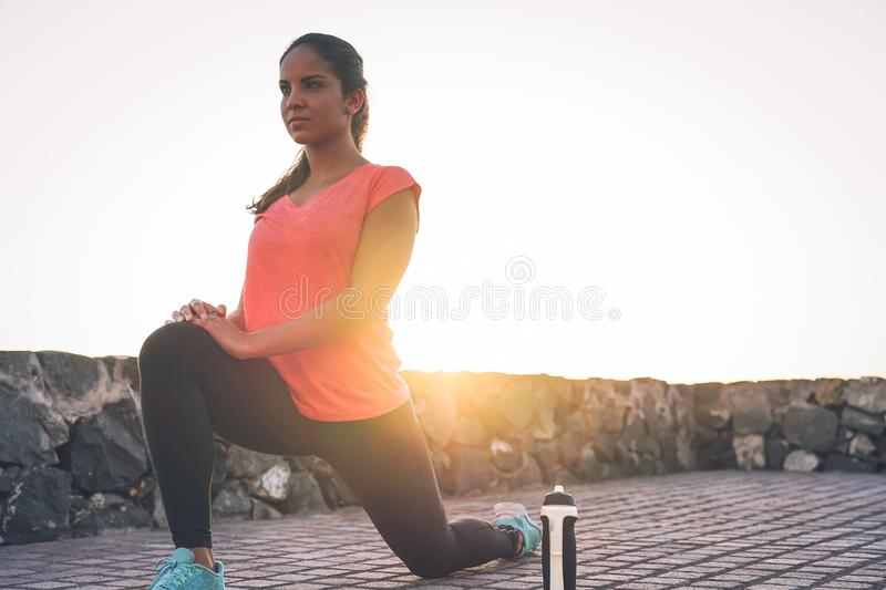 Young attractive woman stretching next the beach during a magnificent sunset - Sporty health girl workout outdoor stock images