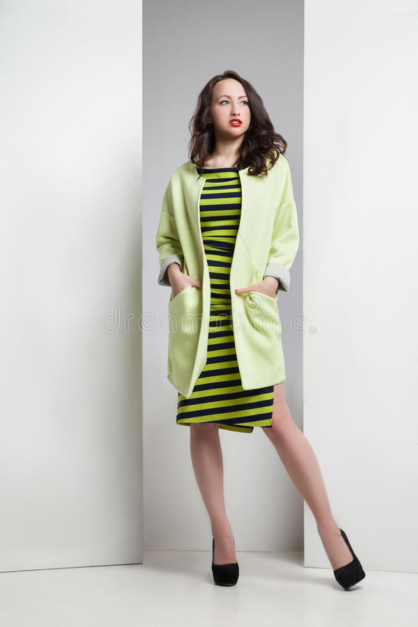 Young attractive woman in striped dress and coat stock images