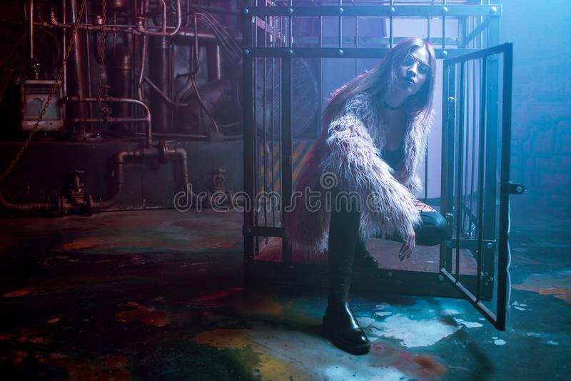 Young attractive woman with stylish clothes. Beautiful girl in fluffy pink fur coat, cyberpunk background. Neon light royalty free stock images