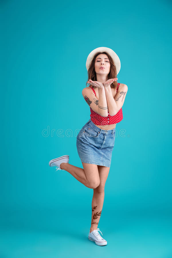 Young attractive woman in summer clothes blowing kiss to camera stock photo