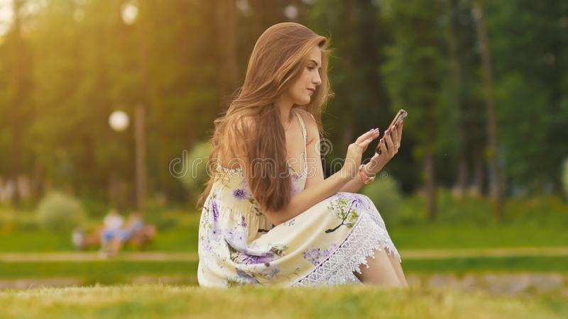 Young attractive woman in summer dress sits on green grass with mobile phone in hands. A park. Summer. Recreation. stock photo