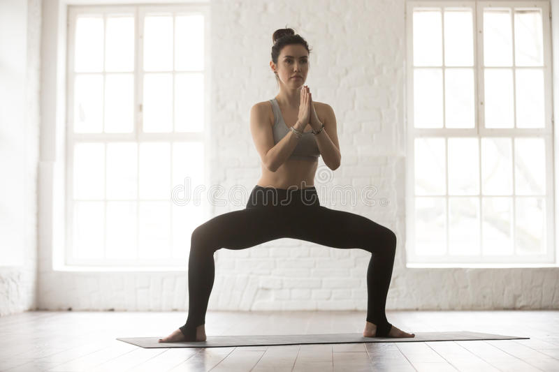 Young attractive woman in Sumo Squat pose, white loft studio. Portrait of young attractive yogi woman practicing yoga concept, standing in Sumo Squat exercise stock image