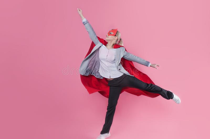 Young attractive woman superhero. Girl in a business suit and a mask with red cloak of hero. stock photo