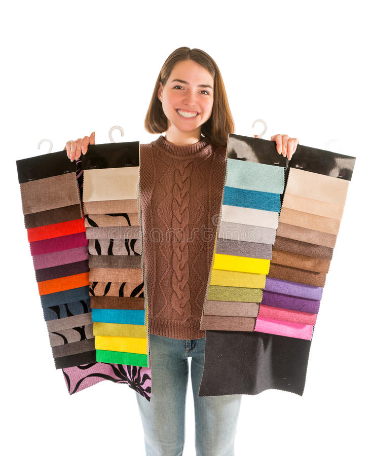 Young attractive woman in sweater holding fabric swatches. Isolated on white background stock images