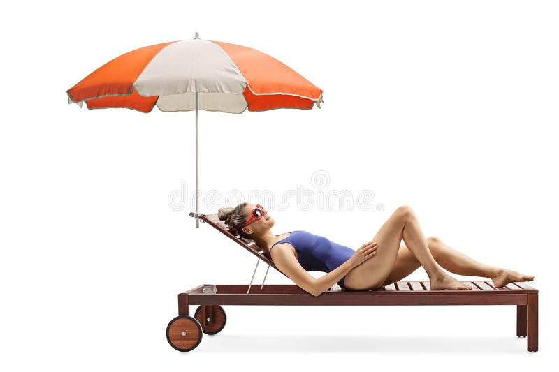 Young attractive woman in a swimsuit lying on a sunbed under umbrella stock photography