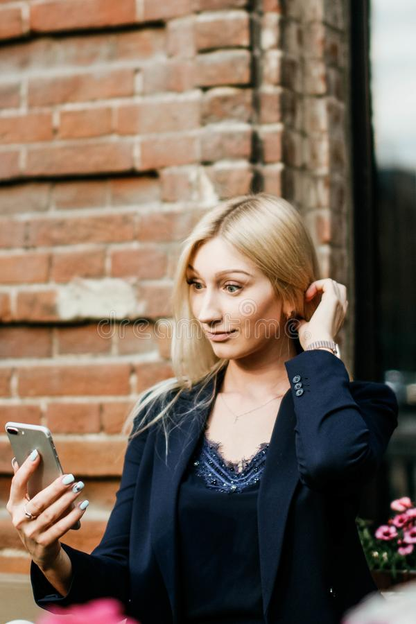 A young attractive woman takes a picture of herself on her smartphone, sitting on a street bench during the lunch break stock images