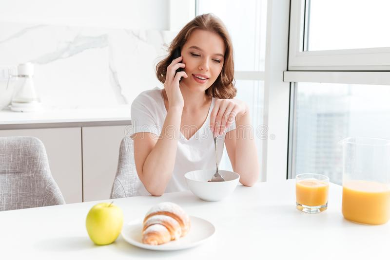 Young attractive woman talking on mobile phone while having breakfast at the kitchen table stock photos
