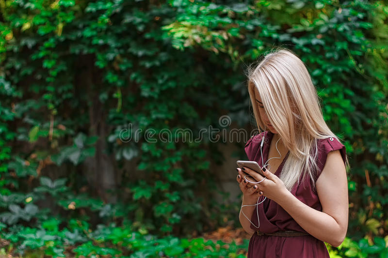 Young attractive woman is texting with her smartphone stock photography