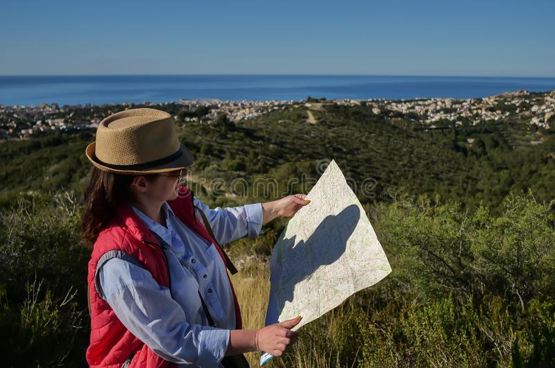 Young attractive woman tourist with hat and map of the area looks at the city under the hill stock photos