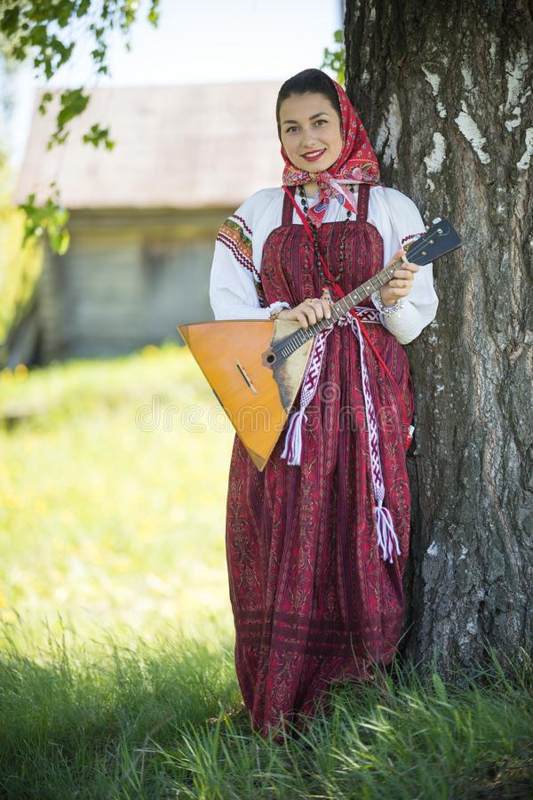 Young attractive woman in traditional russian clothes standing under a tree with the balalaika and posing for a photo. Vertical shot royalty free stock photo