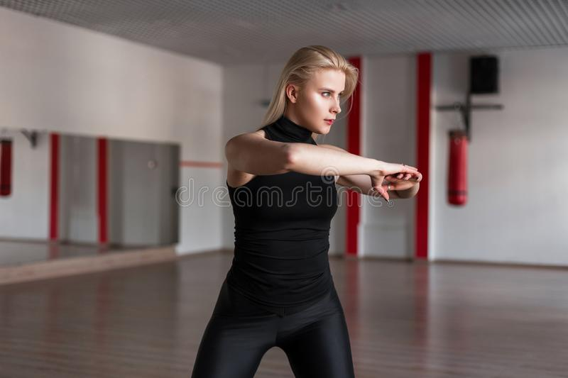 Young attractive woman trainer in a black T-shirt in leggings shows how to do stretching exercises for the back. stock image