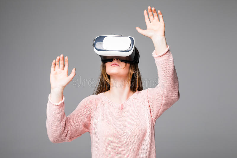 Young attractive woman wearing headset VR virtual reality vision goggles watching video happy amazed and shocked in new advanced t stock photography