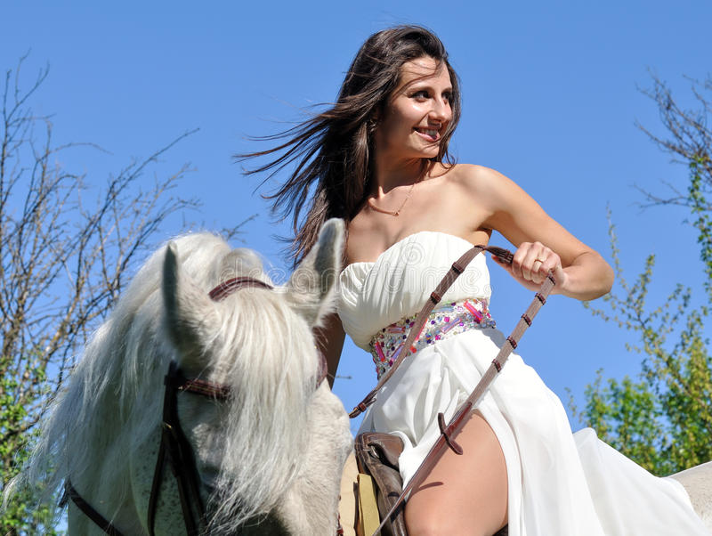 Young attractive woman in white dress with white horse royalty free stock photo