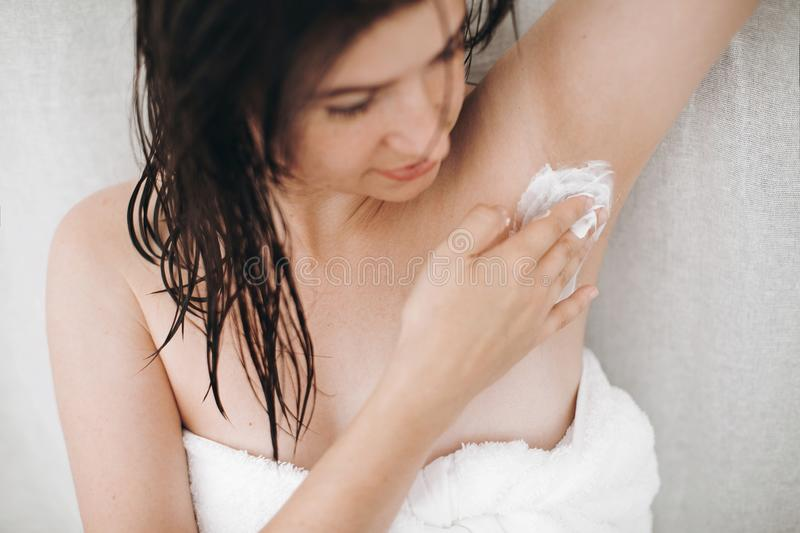 Young attractive woman in white towel applying shaving cream on armpit for depilation in home bathroom. Skin care. Hair Removal. Concept. Woman after shower stock images