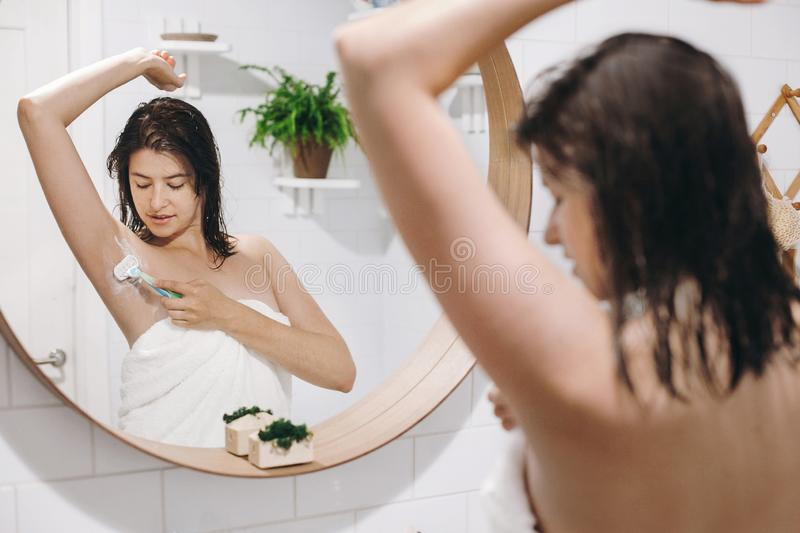 Young attractive woman in white towel shaving armpits, looking in mirror in stylish bathroom. Skin and body care. Hair Removal. Concept. Woman after shower stock photography
