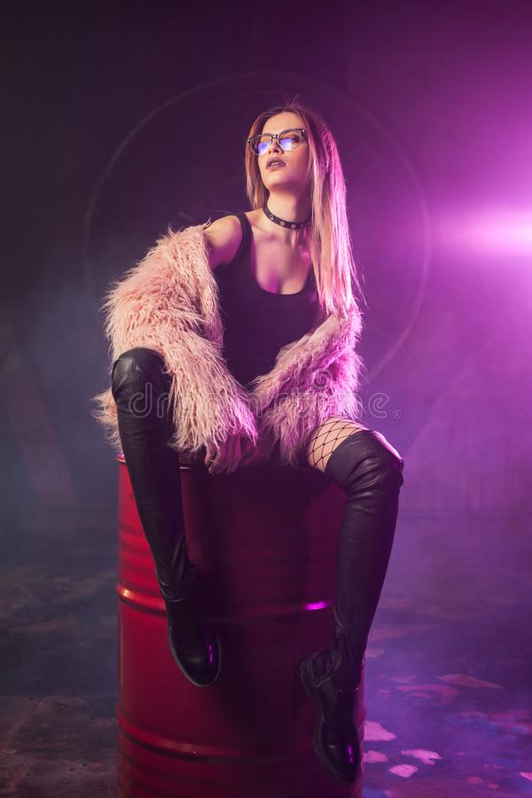 Free Young Attractive Woman With Stylish Clothes. Beautiful Girl In Fluffy Pink Fur Coat Sits On Barrel. Neon Light Royalty Free Stock Photos - 112482318