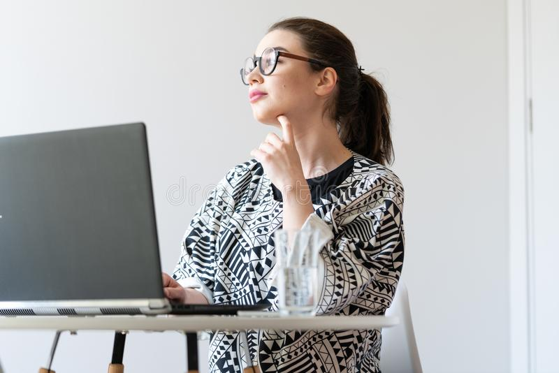 Young attractive woman working on laptop in modern bright apartments royalty free stock photography