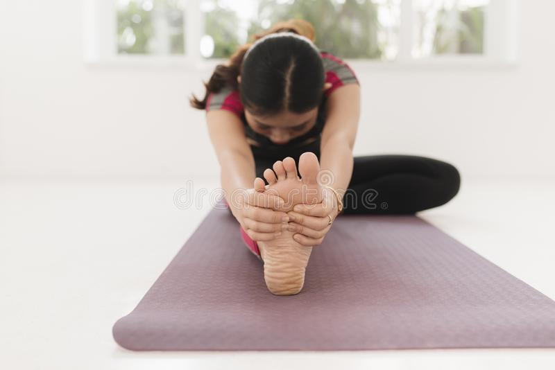 Young attractive yogi woman practicing yoga concept, sitting in Janu Sirsasana exercise, Head to Knee Forward Bend pose, working stock photo