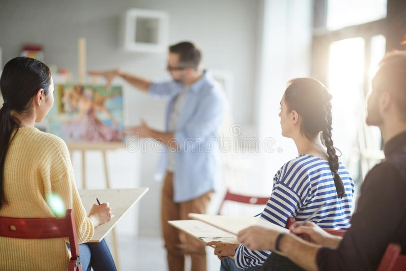 Young audience. Group of young learners making notes while listening to their teacher explanations at lesson of painting royalty free stock images