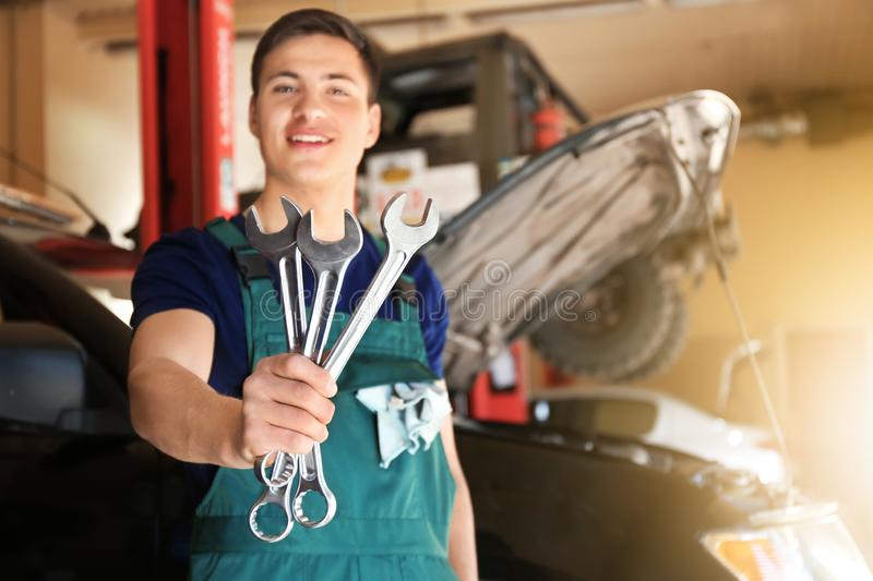 Young auto mechanic with tools near car in service center royalty free stock photography