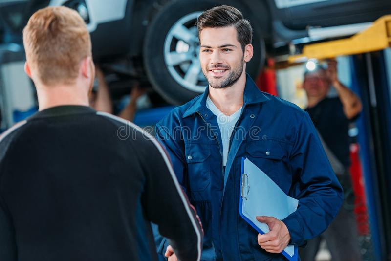 Automechanic welcoming client. Young automechanic with a clipboard welcoming a client at a repair shop stock photography