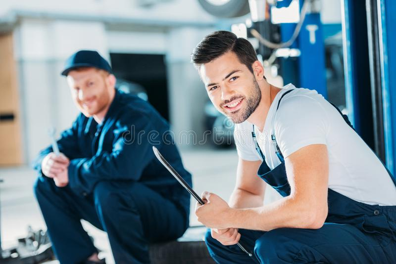 Automechanics sitting on floor. Young automechanics sitting on a floor of a repair shop royalty free stock photos
