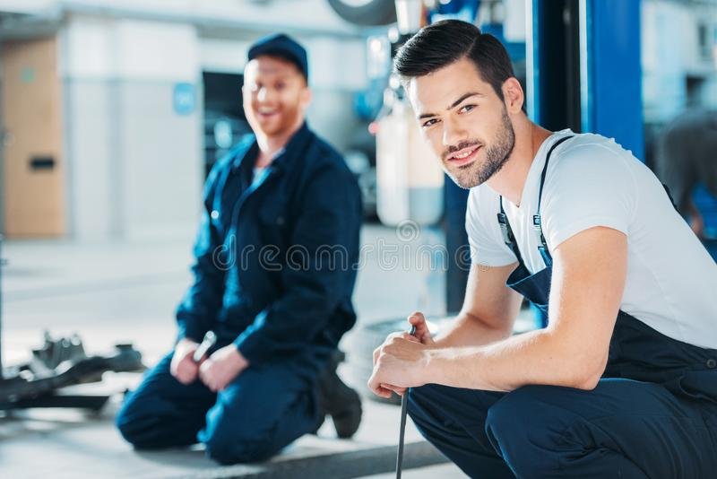 Automechanics sitting on floor. Young automechanics sitting on a floor of a repair shop stock photos