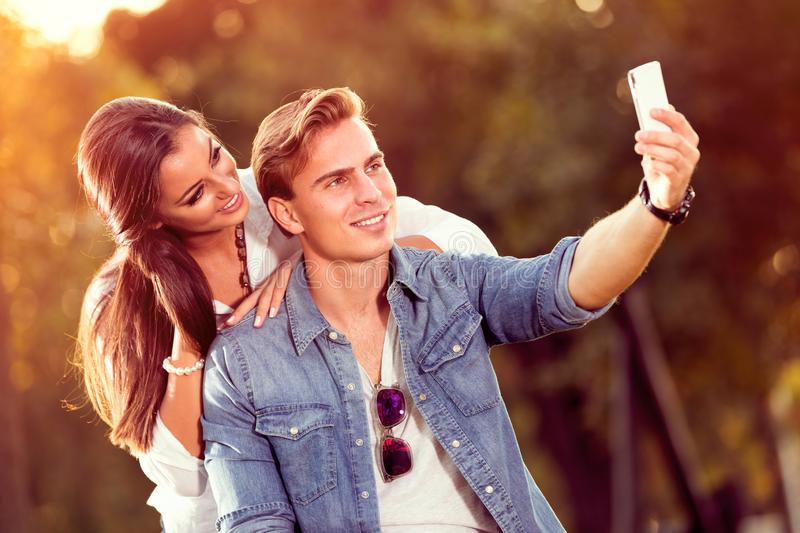 Young autumn couple making selfie royalty free stock image