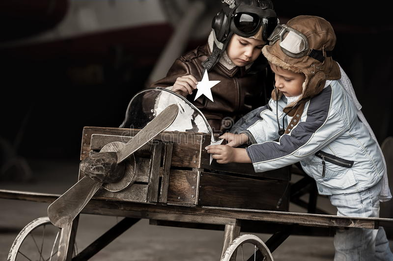 Young aviators. In homemade aircraft in a large hangar royalty free stock photo