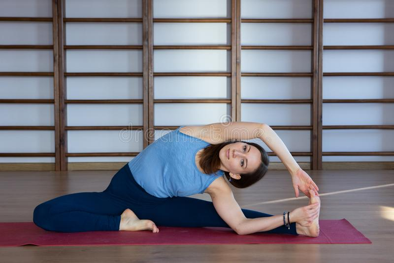 Young awesome happy woman developing flexibility. full length photo.yoga practise. Calmness and relax, female happiness concept royalty free stock photo