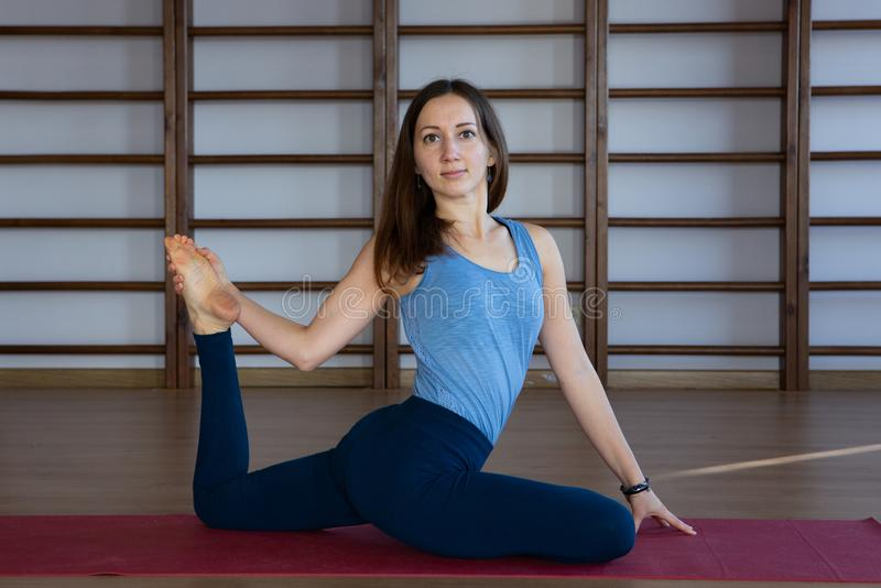 Young awesome happy woman developing flexibility. full length photo.yoga practise. Calmness and relax, female happiness concept royalty free stock photography