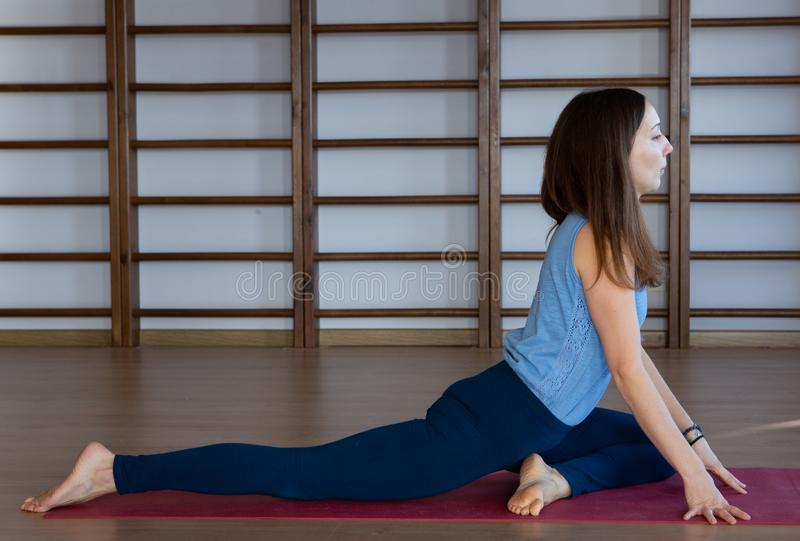 Young awesome happy woman developing flexibility. full length photo.yoga practise. Calmness and relax, female happiness concept stock photo