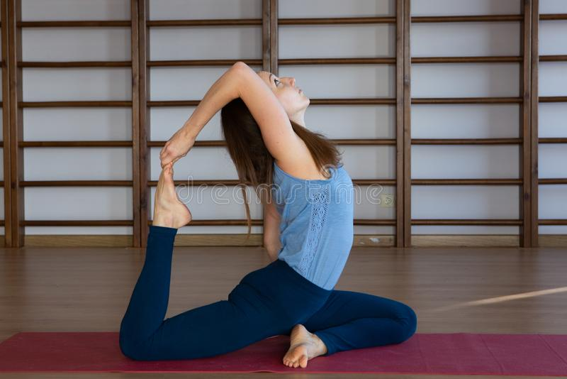 Young awesome happy woman developing flexibility. full length photo.yoga practise. Calmness and relax, female happiness concept royalty free stock image