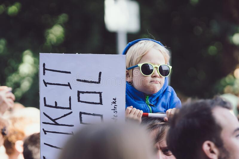 Young baby boy on dad shoulder holding demonstration sign banner. MUNICH, GERMANY - Sep 20, 2019: Young baby boy on dad shoulder holding demonstration sign stock photography