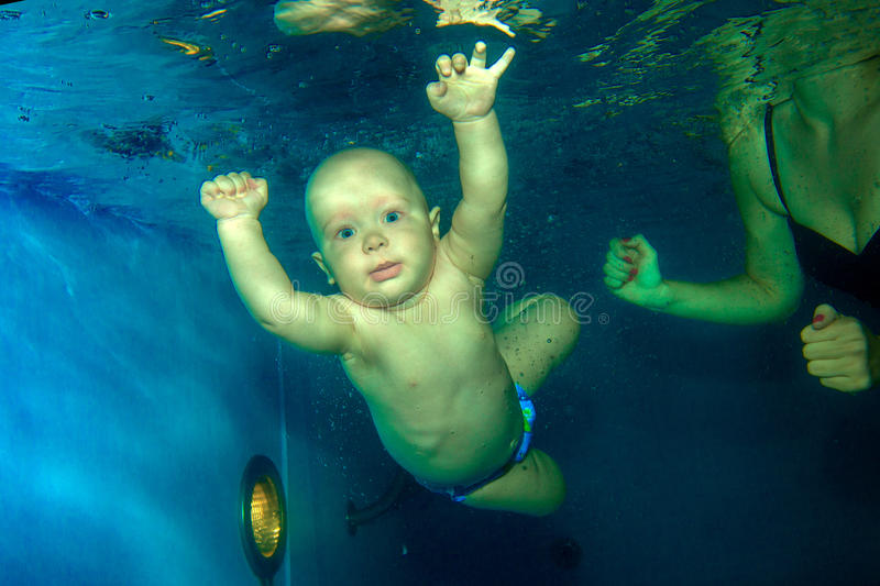Young baby diving in the swimming pool. Young baby diving in the swimming pool royalty free stock images
