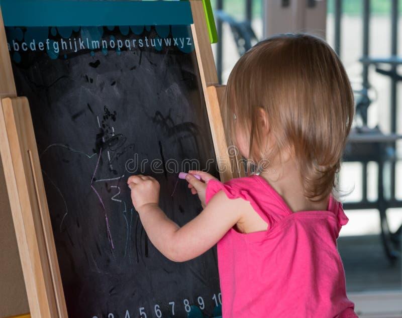 Young baby girl drawing at blackboard stock photo