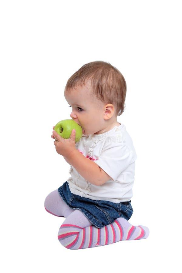 Young baby girl eating fresh green apple stock image