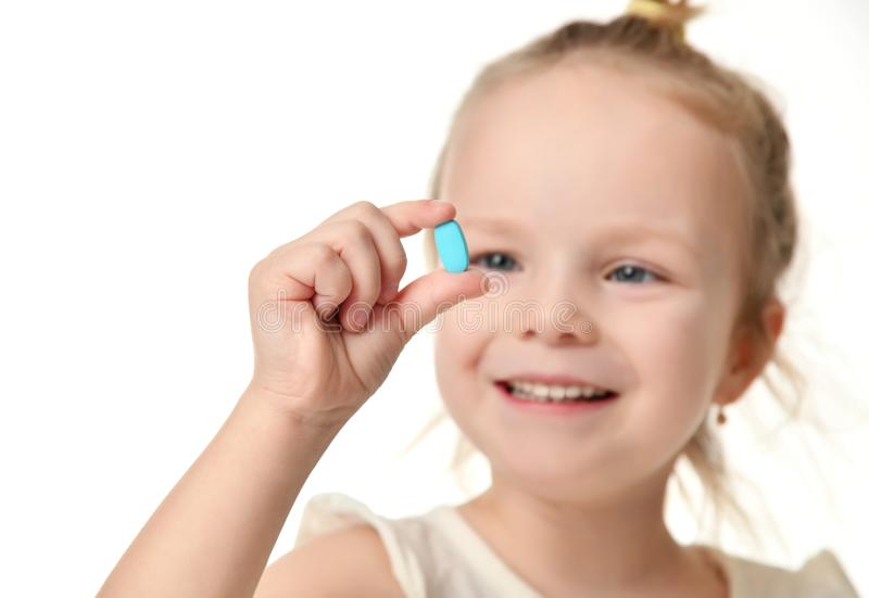 Young baby girl hold light blue headache pill medicine tablet in small hand royalty free stock images