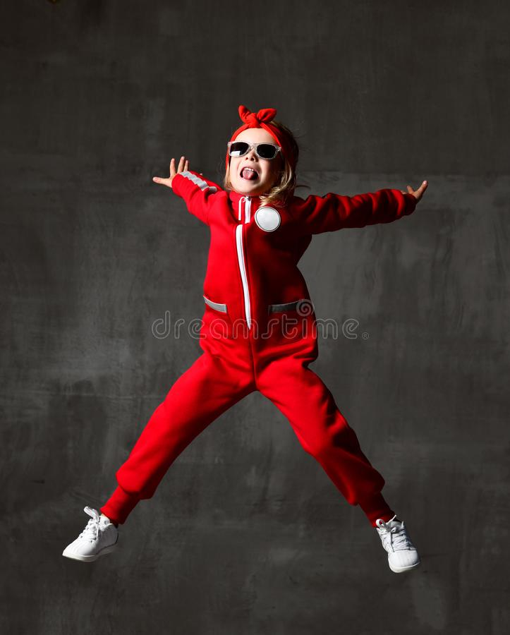 Young baby girl kid jumping in red cloth and sunglasses on dark grey wall royalty free stock images