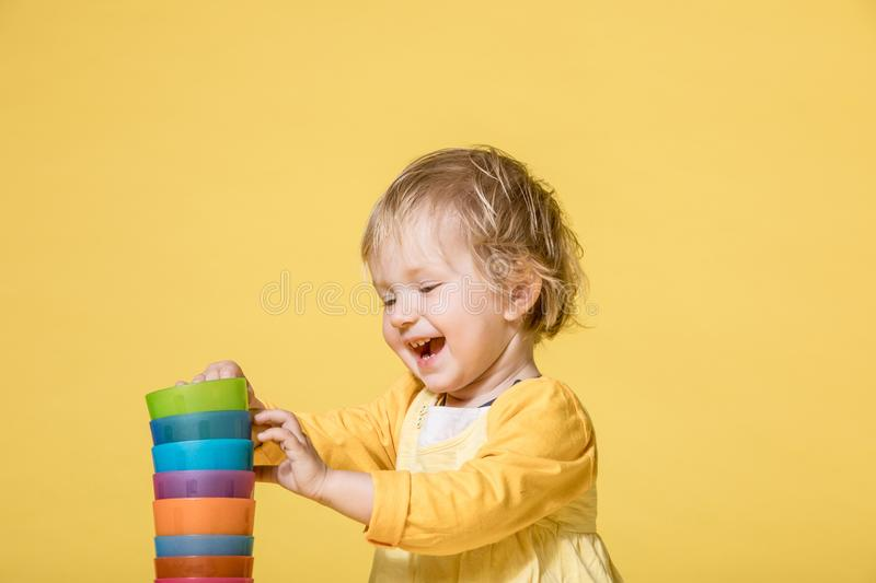 Young Baby Girl in Yellow Dress on Yellow Background royalty free stock photos