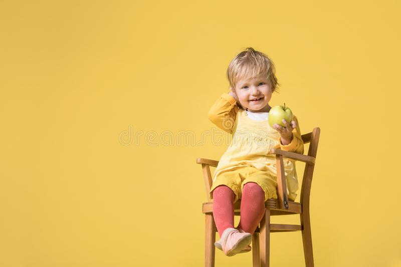 Young Baby Girl in Yellow Dress on Yellow Background stock photos