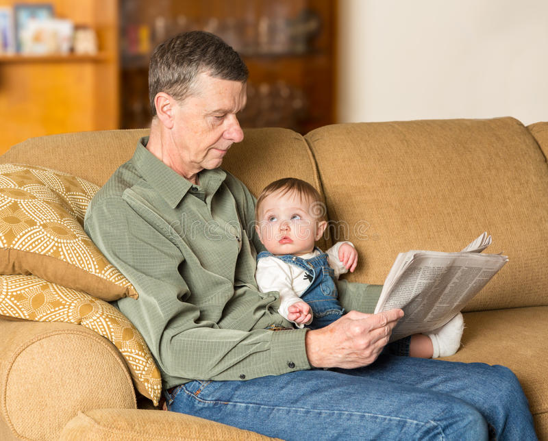 Young baby looking up at grandad with paper. Young caucasian baby girl looking up at grandfather reading newspaper on settee in family room royalty free stock photo