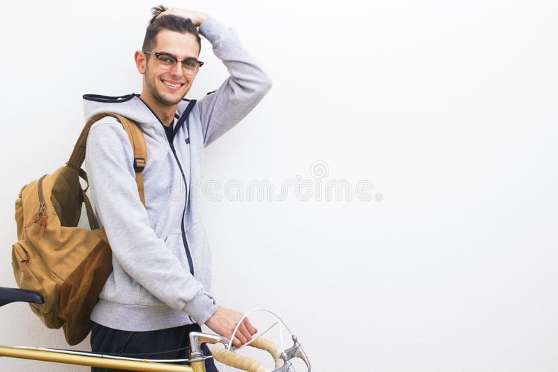 Young with backpack and bicycle. In white wall royalty free stock image