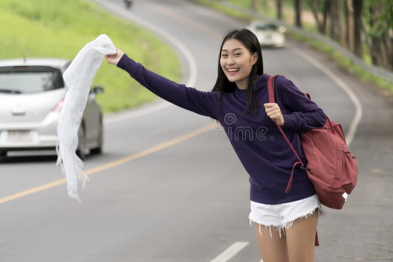 Young backpacker female waving cloth at sidestreet stock photos