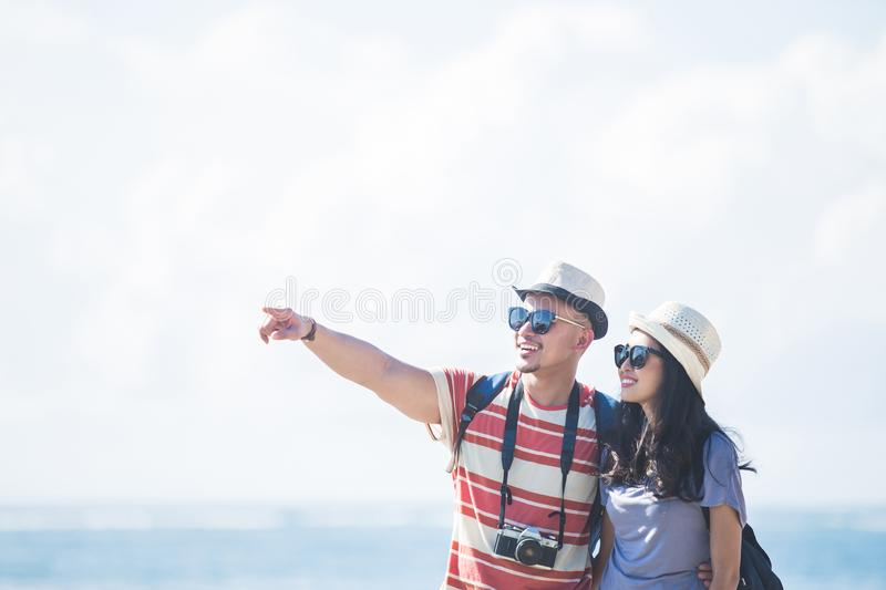 Young backpacker with his partner pointing at something during s. Portrait of young backpacker with his partner pointing at something during summer vacation with royalty free stock photography